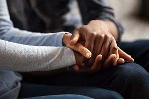 two people holding hands in a support group during outpatient programs