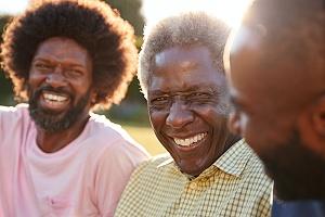three men sitting outside doing peer support
