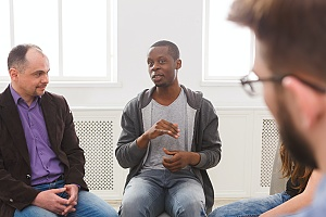 three men sitting in group therapy for Addiction Treatment & Therapies