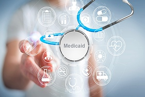 woman pointing to the screen with the word medicaid in a stethoscope