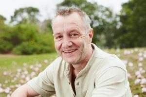 older man smiling in field