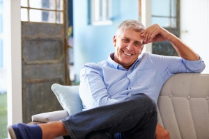 man sitting on couch knowing How Long Is An Intensive Outpatient Program