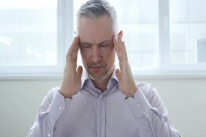 man with headache from not going to rehab for alcohol