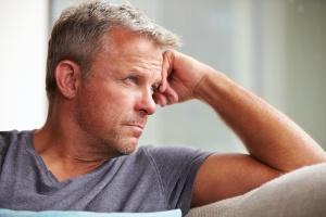 older man looking out window thinking  about rehab for alcohol
